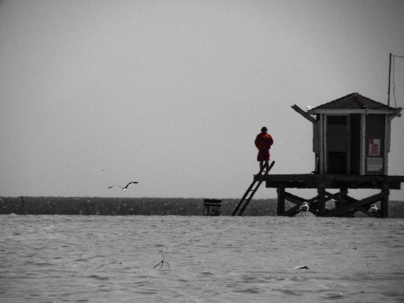 Grey beach, red jacket